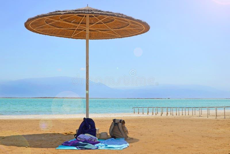 Stroparaplu, rugzakken en sprei op een zandig strand door het water Toerisme en rust op het Dode Overzees in Israël royalty-vrije stock foto