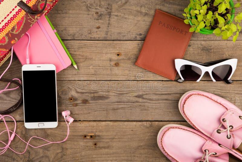 strozak, slimme telefoon, hoofdtelefoons, zonnebril, blocnote, roze schoenen en paspoort op houten bureau royalty-vrije stock afbeeldingen
