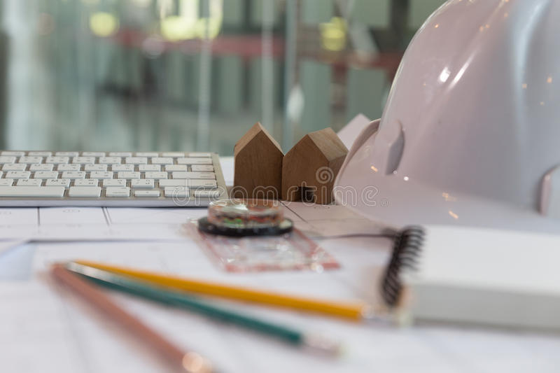 Structural engineer and architect desk with safety helmet, blueprint and model house stock photos