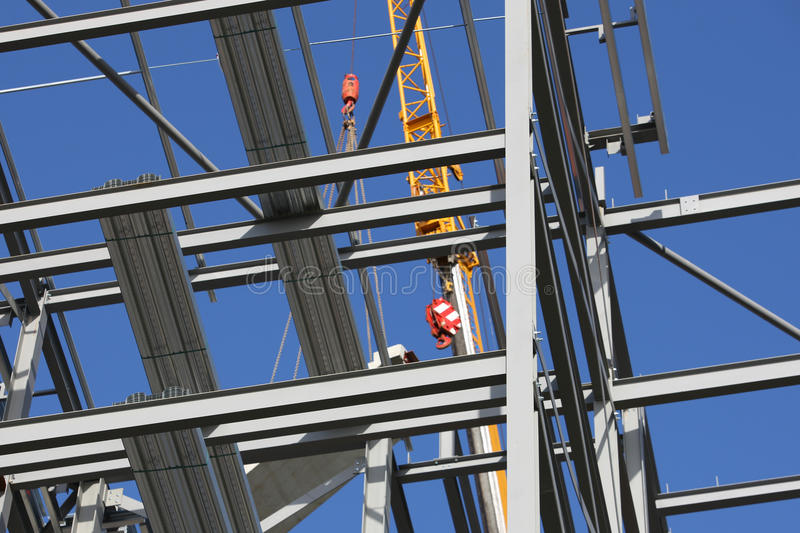 Structural Steel Framework with Crane. Structural steel framework for new appartment block with crane in soft focus behind. Sharp focus on foreground girders stock images