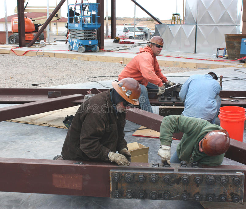 Structural truss connectors. A group of ironworkers bolt-up structural truss sections for lifting into place on a roof structure royalty free stock photography
