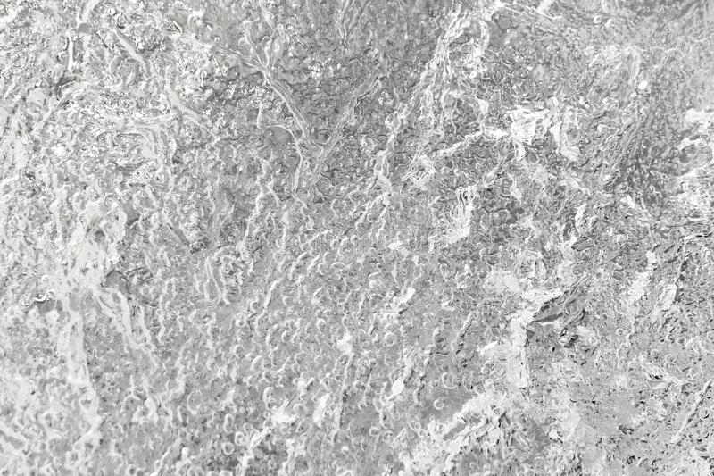 A structure and stains of frozen fragility water in black and white color. abstract natural background. A structure and stains of the frozen fragility water in stock photos