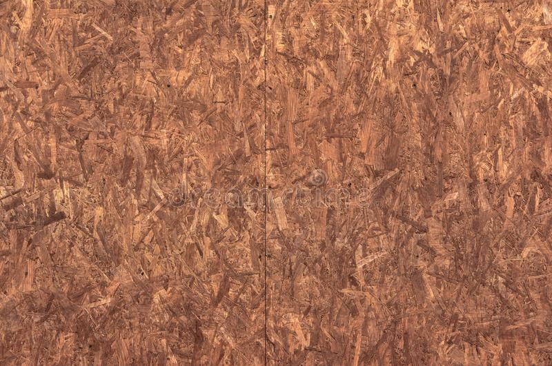 The structure of the wood chipboard, painted in red-brown color close-up. Abstract background.  royalty free stock photography