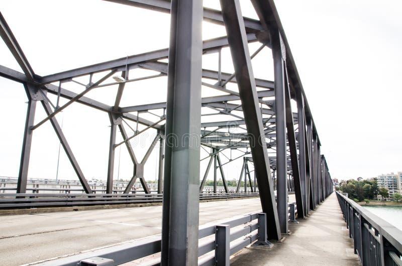 Structureel staalbrug die de rivier en opzij met cycleway kruisen royalty-vrije stock afbeelding