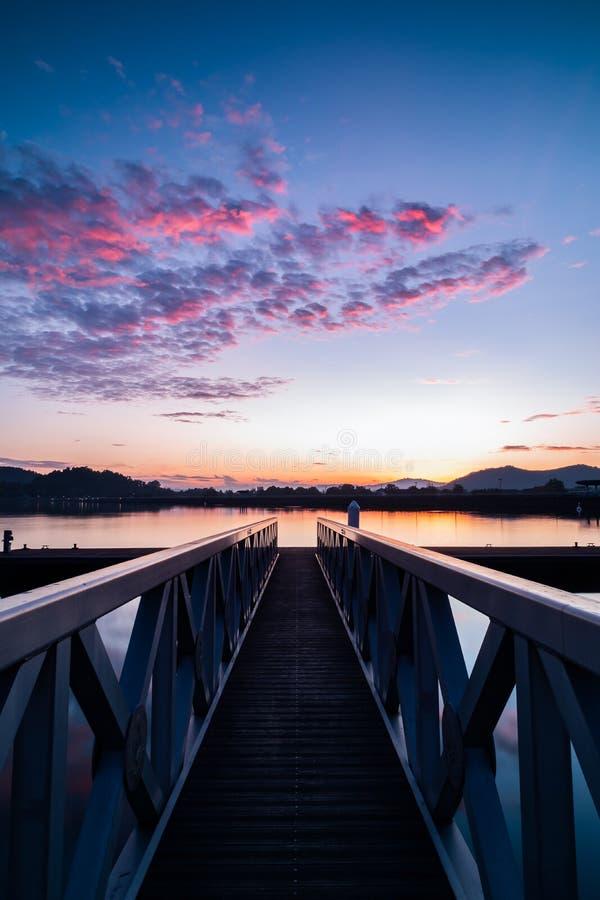 Structuur van de pier die tot de mooie zonsopganggloed leiden stock foto