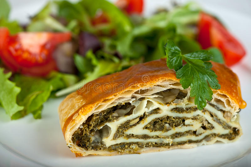 Strudel. Spinach strudel with fresh salad royalty free stock image