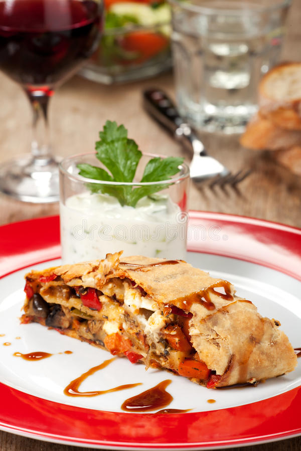 Strudel. Vegetable strudel on a plate with salad stock photos