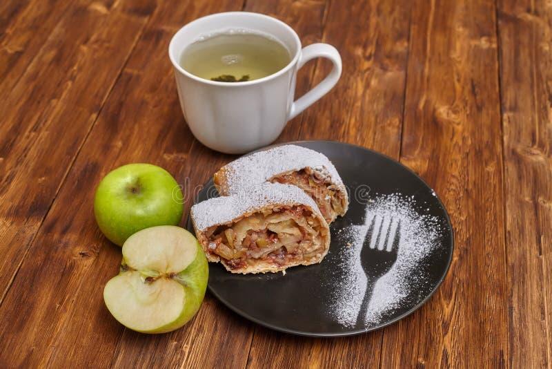 Strudel alle mele con lo zucchero a velo sulla banda nera, fondo di legno fotografie stock