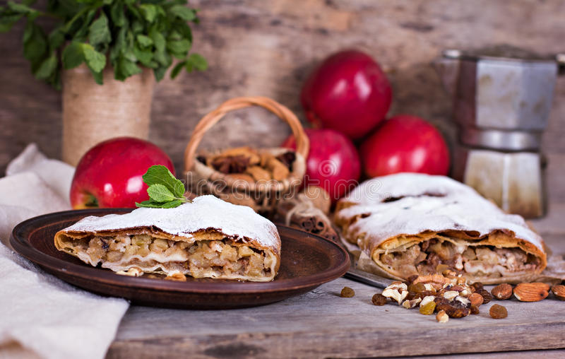 Strudel with apples and nuts. Sliced homemade apple strudel served with fresh apples, cinnamon sticks and sugar powder over old wooden background. Close up royalty free stock photo