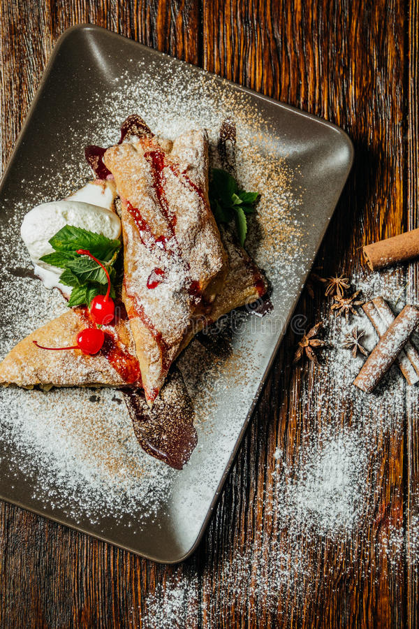 Strudel cake in plate with cinnamon, sugar powder on rustic wooden table background royalty free stock photo