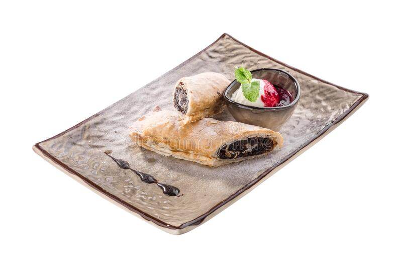 Strudel dessert with plum and ice cream on grey plate isolated on white background. Side view royalty free stock photos