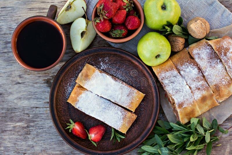 Strudel med äpplen och jordgubbar arkivfoto