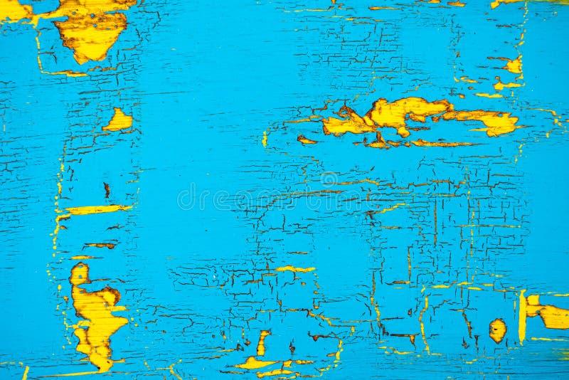 Strugać, pękam błękit i kolor żółty malowaliśmy drewnianego tło fotografia stock