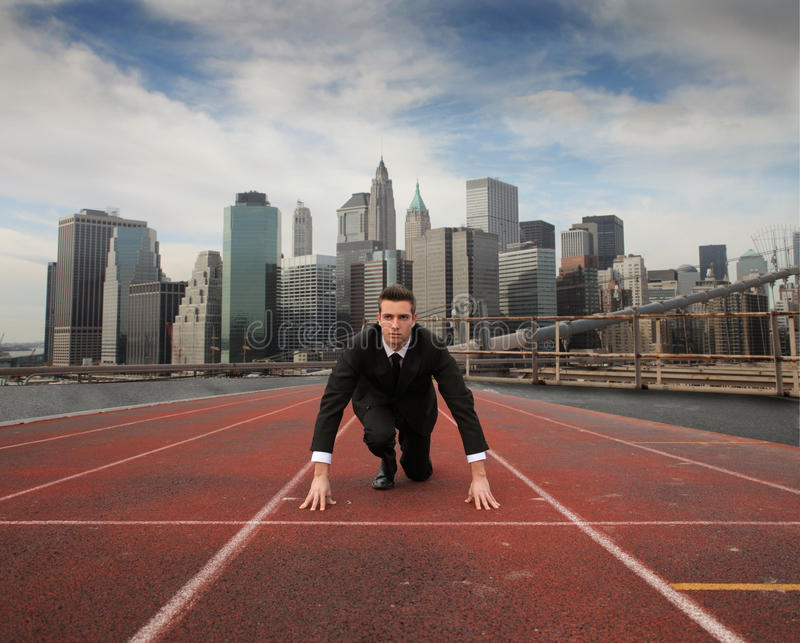 Struggle. Businessman on a starting grid with cityscape on the background