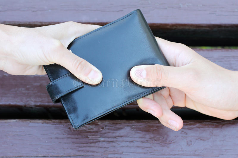 Struggle for the purse. Black purse dragging in different directions two human hands stock photography