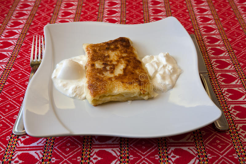 Strukle with cream - famous Croatian appetizer. Made with fresh cheese from the Zagorje region on a table cloth with traditional pattern from Zagorje region royalty free stock image