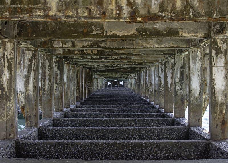 Strukturelle konkrete Spalten und Strahlen unter der Brücke wurden in Meer geschädigt lizenzfreie stockbilder