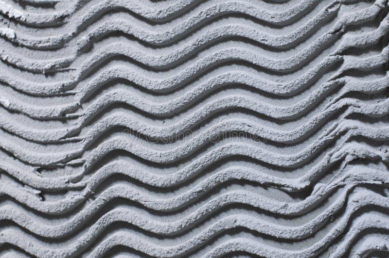 Struktureller monophonischer Hintergrund des Gipsgipsgraus, mit einem Muster in Form von Wellen lizenzfreie stockbilder