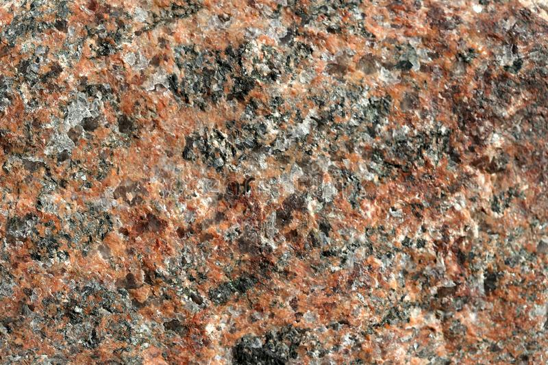 Strukturen av naturlig inte jordorange granit med svarta åder arkivbild