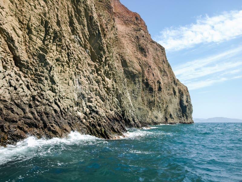 Strukturierte steile Felsen des vulkanischen Ursprung auf der Seeküste lizenzfreie stockbilder