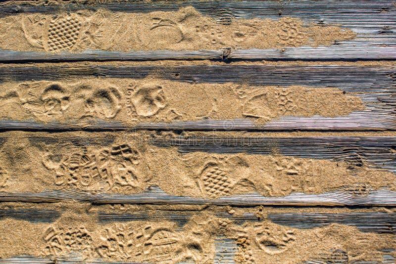 Strukturierter ausführlicher hölzerner Bodenbelag von den Planken auf dem Sand auf dem Strand mit Abdrücken von Schuhen stockfotografie