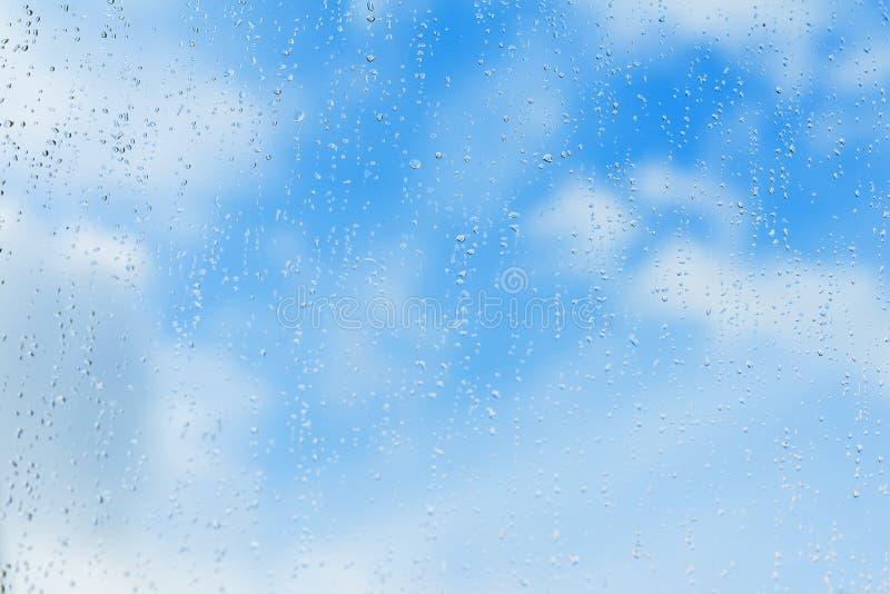 Strukturierter blauer Hintergrund des Himmels, Rohwasser fällt auf Fensterglas, Regenbeschaffenheit Konzept von klarem, rein, hel lizenzfreie stockfotos