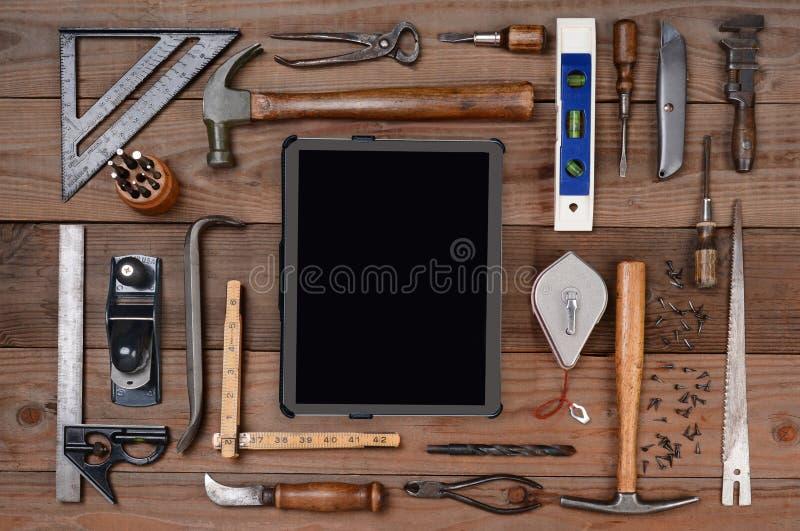 Strumenti degli appaltatori con il computer della compressa fotografia stock