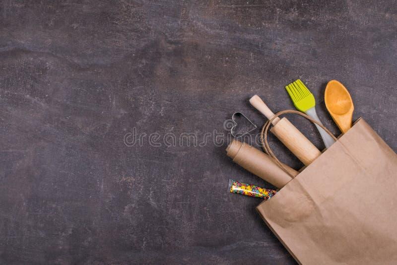 Strumenti del forno nella borsa riciclata del mestiere di carta L'insieme bollente del dolce, gli strumenti del forno, bakeware m fotografia stock libera da diritti