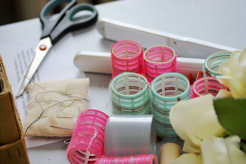 Strumenti del parrucchiere Bigodini, forbici, filo con gli aghi fotografia stock