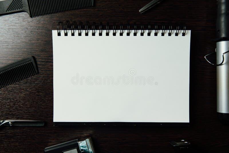 Strumenti del parrucchiere su fondo di legno scuro Blocco note della carta in bianco con la disposizione del piano degli accessor fotografia stock libera da diritti