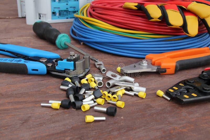 Strumenti dell'elettricista con cavo rosso e blu presentato su una superficie di legno di colore scuro Vista superiore immagine stock libera da diritti