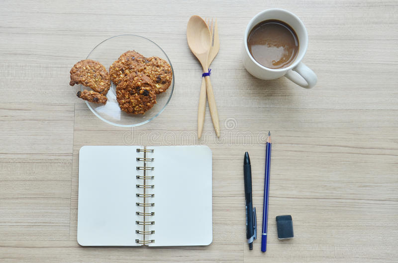 Strumenti della carta in bianco, della pausa caffè e dell'ufficio sulla tavola di legno - T immagini stock