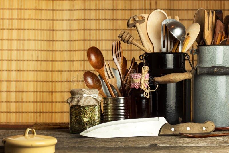 Strumenti della cucina sulla tavola Utensili per i cuochi unici Vecchio cucchiaio di legno immagine stock libera da diritti