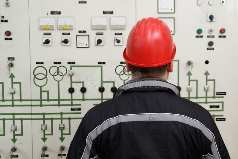 Strumenti della lettura del tecnico nel centro di controllo della centrale elettrica fotografia stock libera da diritti