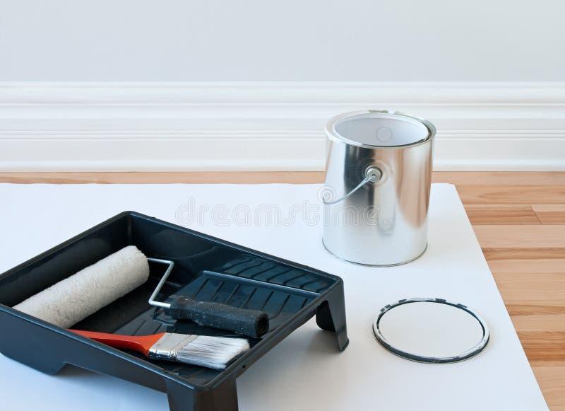 Strumenti della pittura e latta di vernice fotografia stock
