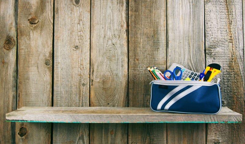 Strumenti della scuola in un caso Su fondo di legno immagini stock libere da diritti