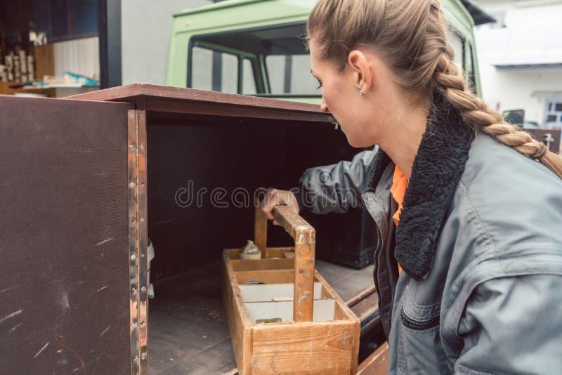 Strumenti di caricamento del carpentiere della donna nel trasportatore mobile dell'officina immagini stock libere da diritti