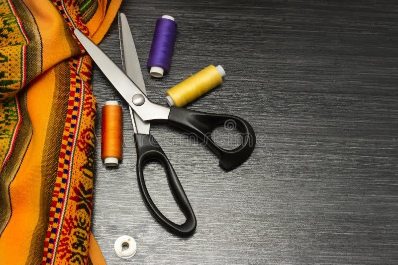 Strumenti di cucito: panno variopinto le forbici ed il corredo di cucito includono i fili dei colori differenti, del ditale e di  immagine stock libera da diritti