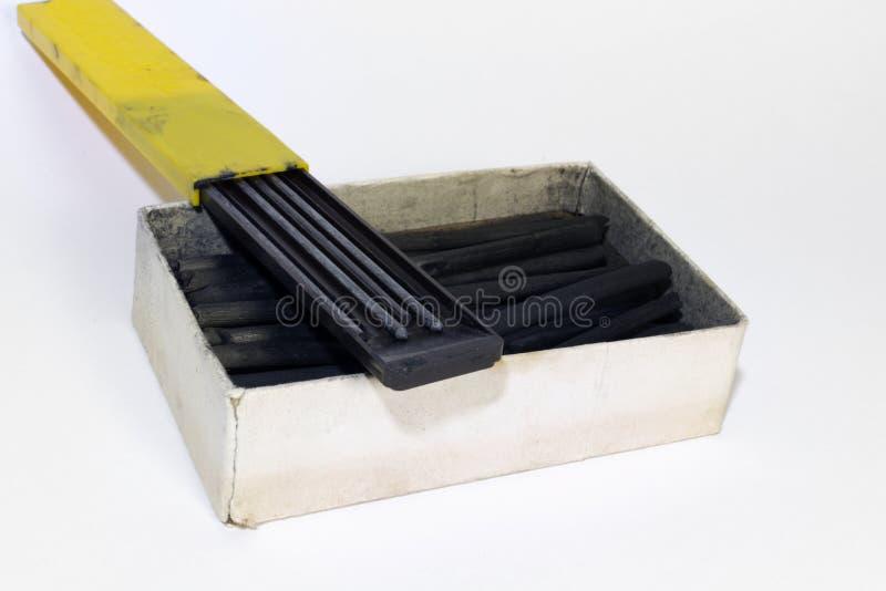 strumenti di disegno: I vecchi bastoni del carboncino e la grafite woodless del monolito disegnano a matita nei casi fotografie stock