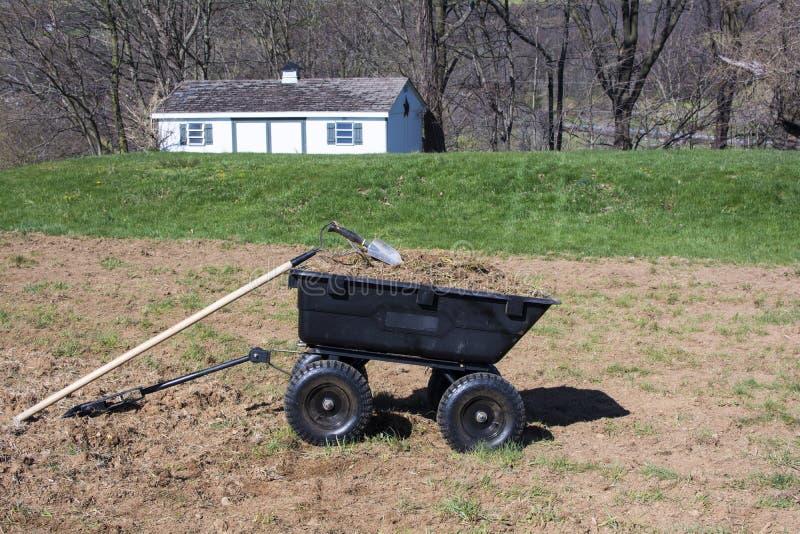 Strumenti di giardinaggio su sporcizia e su erbe in carretto dell'iarda fotografie stock