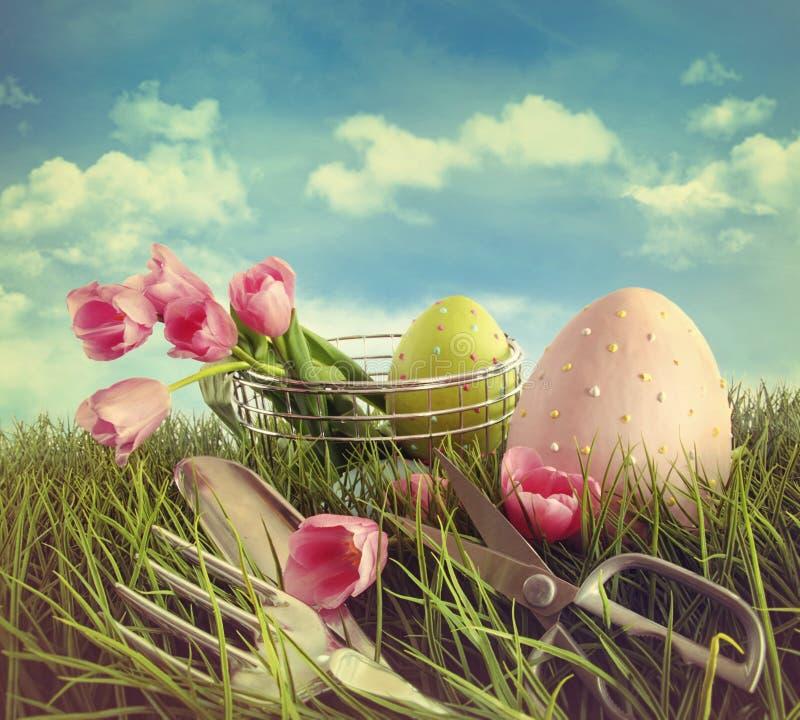 Strumenti di giardino dei tulipani ed uova di Pasqua nel campo fotografia stock libera da diritti