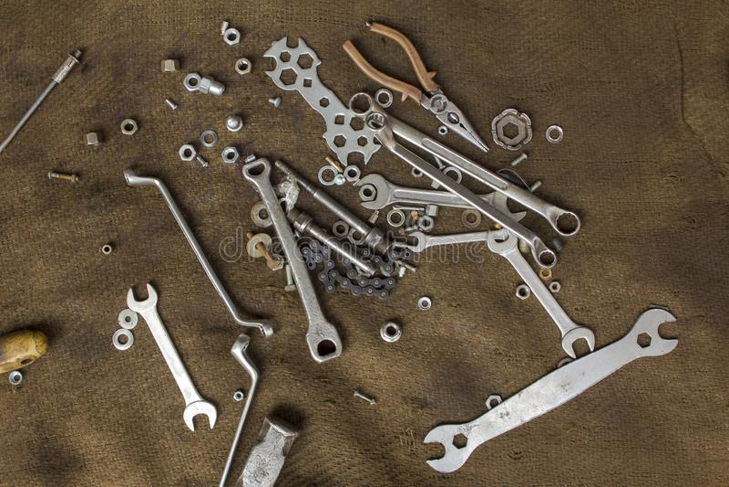 Strumenti e dadi anziani del metallo su un primo piano sporco della tela da imballaggio Struttura della superficie ruvida immagini stock