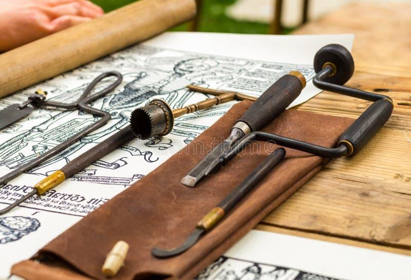 Strumenti medici medievali, interventi chirurgici d'avanzamento di un inventario tradizionale del guaritore su un fondo di legno immagini stock