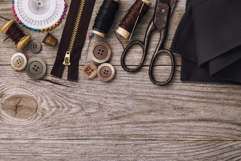 Strumenti per la riparazione e vestiti di adattamento sulla tavola di legno immagini stock