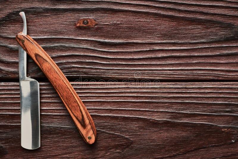 Strumento d'annata del rasoio diritto del negozio di barbiere su fondo di legno immagine stock libera da diritti