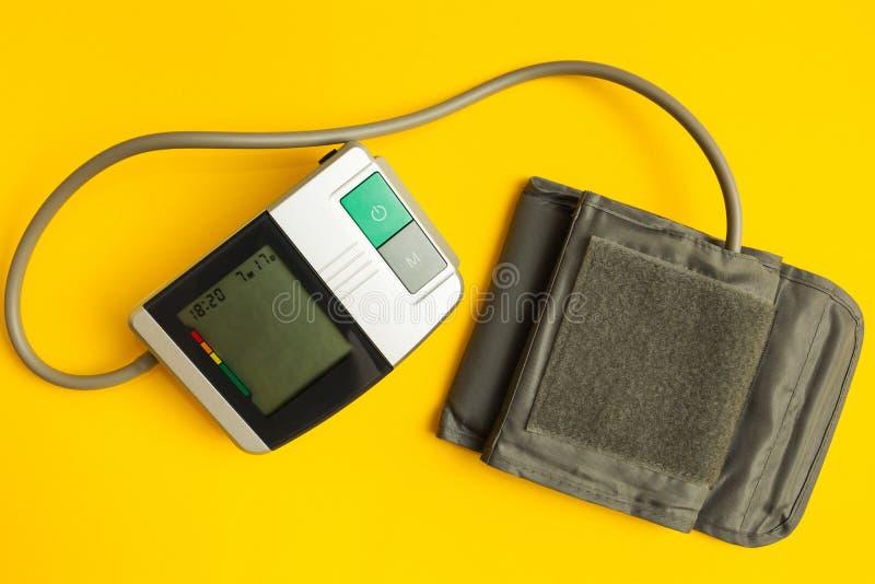 Strumento di Digital per pressione sanguigna di misurazione su un fondo giallo immagini stock
