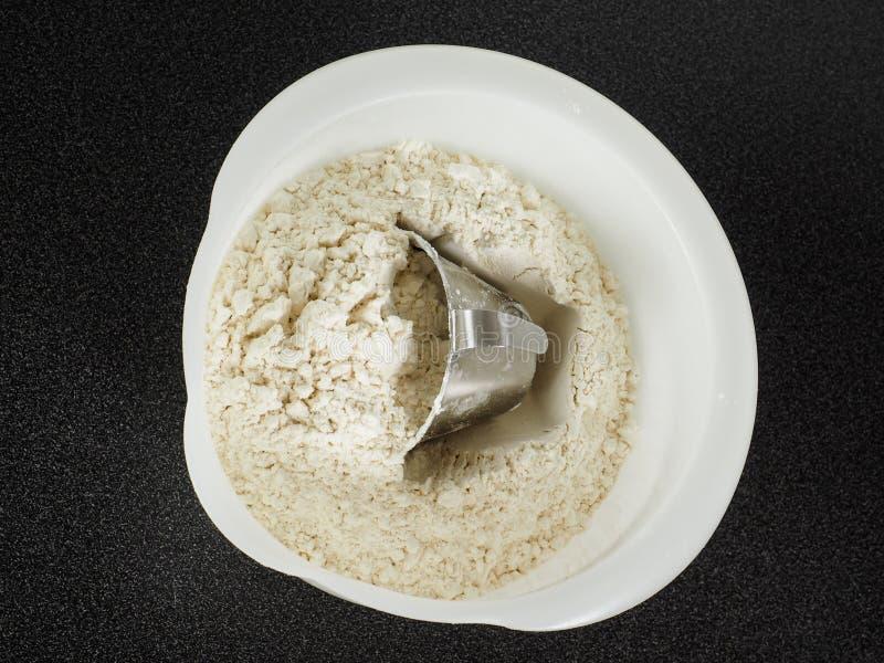 Strumento di misura in una ciotola di farina di frumento fotografia stock libera da diritti