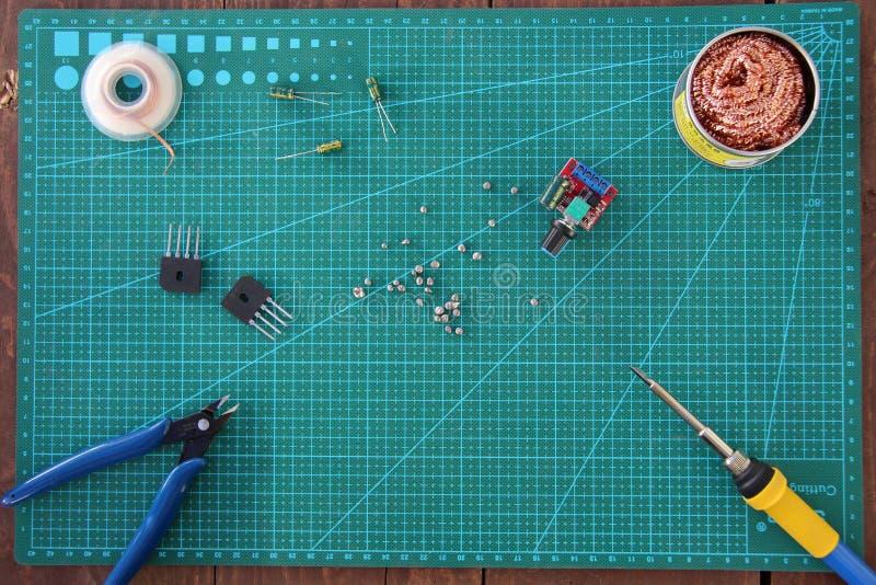 Strumento di riparazione di elettronica sulla tavola su una vista superiore del substrato verde immagine stock