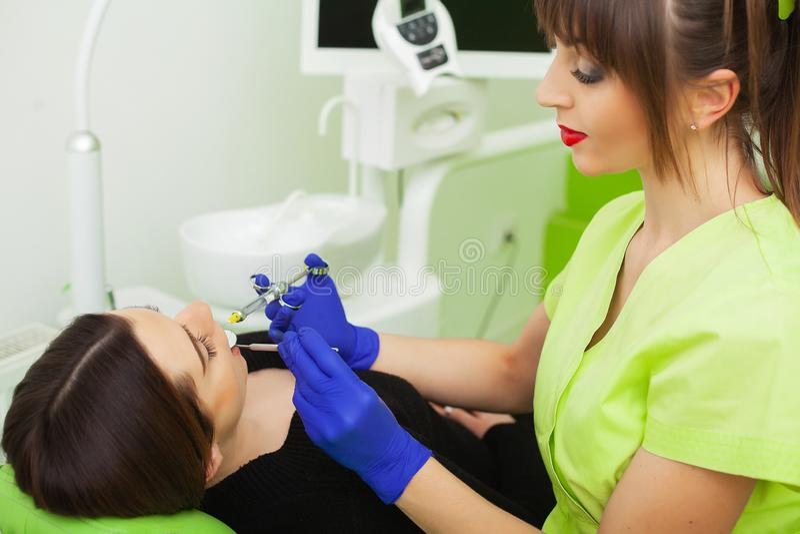 Strumento e siringa di tenuta delle mani del dentista in mani Antidolorifico nell'azione Il cliente femminile tiene la bocca aper immagine stock libera da diritti