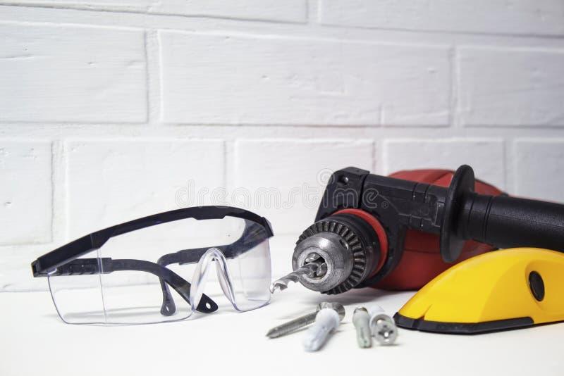 Strumento professionale per perforare Trapano elettrico con gli occhiali di protezione su un fondo del muro di mattoni immagini stock